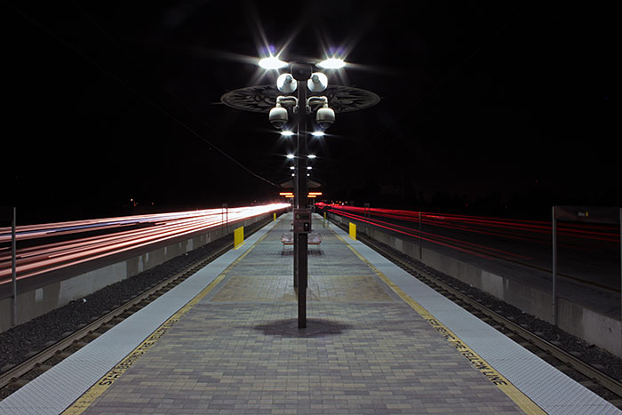 Traffic passing the empty Allen Station platform at night